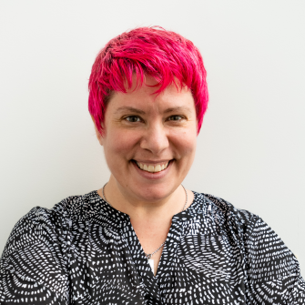 Pale-skinned woman with red/pink hair smiles at camera