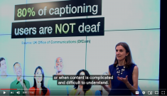 "A woman in a blue dress standing in front of a slide saying: ""80% of captioning users are NOT deaf"" with text in front of her saying: ""or when content is complicated or difficult to understand"""