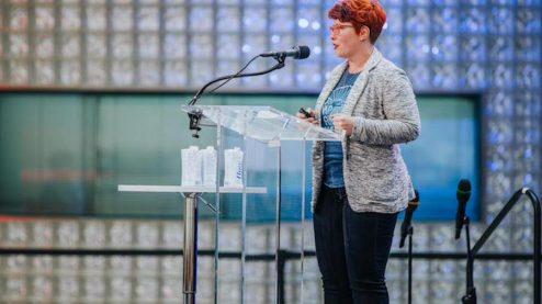 A woman with a red pixie haircut and orange glasses standing at a clear podium and speaking into a microphone. There is a lighted glass block wall behind her and blurry audience member heads in the foreground.